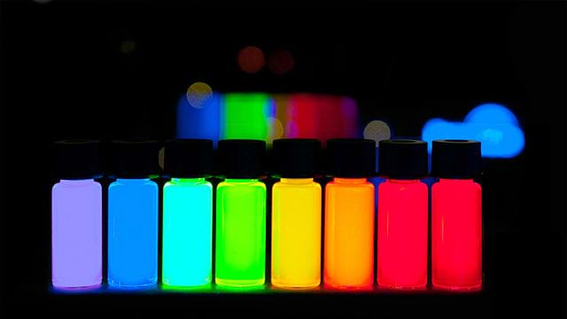 A photograph shows small tubes of manufactured quantum dots of vivid colors ranging from violet to deep red.