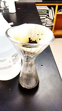 Photo of a funnel filter over a 500 ml flask.  The filter is removing pieces of tea after brewing.