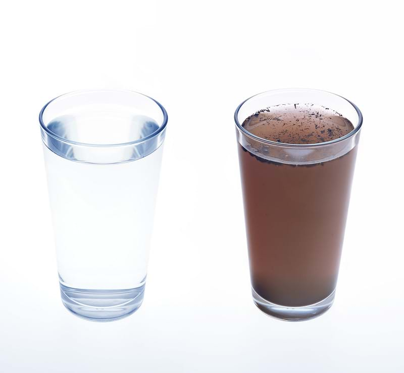 A glass of clean, clear water next to a glass of dirty water, photographed on a white background.
