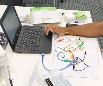 A photograph shows a student's arm as he codes the Circuit Playground to work with the visible circuit.