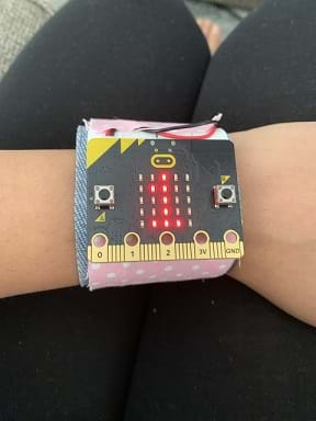 A micro: bit pedometer is worn on a person's wrist. The pedometer has a digital display in red showing the number 1.