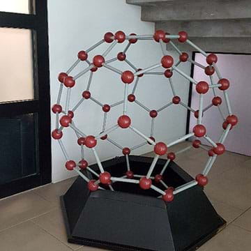 A photograph of a large three-dimensional ball-and-stick model of a buckyball, a carbon-60 molecule, sitting on a support stand.