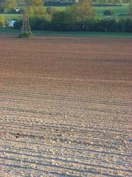 A photograph shows acres of exposed soil prepared for agricultural purposes.