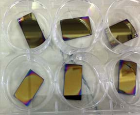 A photograph shows six silicon wafers coated with a doped polystyrene film. The rectangular pieces are mostly a reflective brass color with shades of orange, red, blue and purple at the corners and edges. The color variations indicate thickness variation.