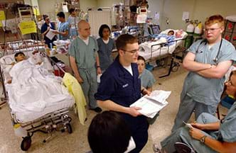 A photograph in an open hospital ward with many patients in beds and many medical workers and a clinical engineer conducting a meeting.