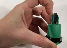 A photograph shows a hand positioned to remove a plastic clip from one end of a threaded green and black plastic device.