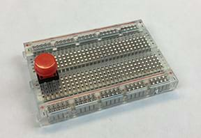 A photograph shows a breadboard with a red pushbutton placed so that one pair of its legs is on either side of the breadboard gap.