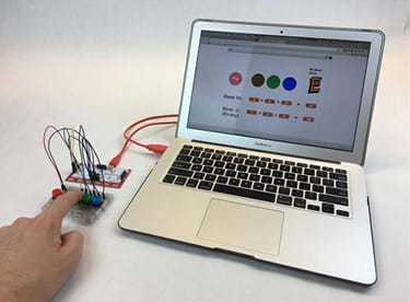 A photograph shows a laptop connected by a USB cable to a MaKey MaKey that is wired to four colored pushbuttons. A finger presses one button. On the screen is the binary trumpet program.