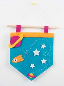 A photograph shows a finished light-up pennant made from felt that is hanging from a wooden dowel and string with a push-pin into the wall. On the pennant, multi-color felt cutouts depict a space scene with planets, stars and a rocket.