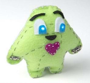 "A photograph shows a plump, blob-shaped ""plush"" toy creature with loosely shaped arms and legs, light-up cartoon eyes (from sewn-in circuit with LEDs), eyebrows and a red heart made of stitched green felt."