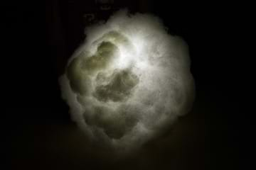 A photograph taken in a dark room shows a paper lantern orb that is entirely obscured by glued-on white fluffy polyfil material and lit by a flashlight held in the center of the lantern/cloud.