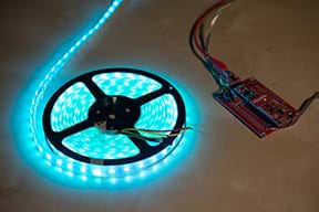 A photograph shows an Arduino on a tabletop next to an illuminated string of blue LED lights coiled on a reel.