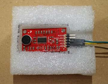 A photograph shows a small red sound detector (circuit board) with header pins connected using female-to-female jumper wires, nestled into a rectangular cut-out in a piece of white packing foam.