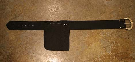 A photograph shows a square black pocket that was cut out of a jacket and sewn onto the middle section of a black belt with buckle and holes.