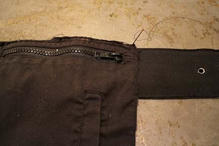 A photograph shows a needle and thread being used to sew the top of a zippered black fabric jacket pocket so it hangs from a belt.