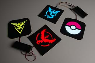 A photograph shows four Pokémon character patches: yellow Zapdos, blue Articuno, red Moltress, and white/pink poke ball. Two patches are each connected to a battery pack.