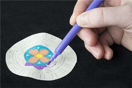 A photograph shows a hand holding a fine-tipped purple marker and coloring in a flower design on white fabric, which is the front of the pin.