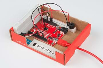 A photograph shows a SparkFun RedBoard attached to breadboards and a potentiometer—all located inside a cardboard box with no lid.
