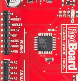 A photograph shows a close up of the SparkFun RedBoard so that you can see black lines (traces) from its center black square chip—its different pins.
