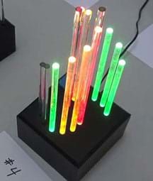 A photograph shows a student-created light sculpture composed of a dozen glowing clear sticks of different heights and colors positioned vertically in a black rack.