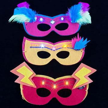 A photograph shows three eye masks made of purple, yellow and pink felt with lighted LEDs above the eye holes, and additional decoration from glued-on feathers and lightning bolt felt cutouts.