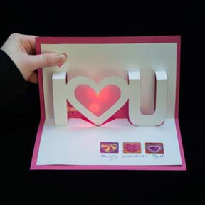 "A photograph shows a hand opening a red and white pop-up and light-up valentine card that says ""I <heart> you."""