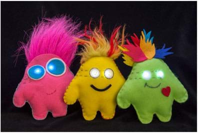 "A photograph shows three plump ""plush"" toys made of felt, each embedded with a LilyPad microcontroller and two LEDs as glowing eyes. The monster blob shapes loosely indicate arms and legs, with faux fur and felt feather shapes sewn into the top seams as hair."