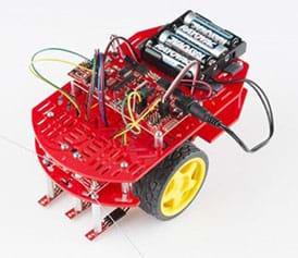 A photograph shows a two-wheeled robot with a two-level red plastic platform covered in oblong holes, on which a circuit board, wires and four batteries are attached to the top level.
