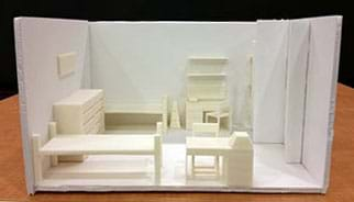 "A photograph shows a diorama-type scale model of a dorm room that looks like a box with the top and one long rectangular sides open. Inside the ""box"" is assorted 3D-printed furniture along the walls (two beds, two desks, two chairs, two dressers, two bookshelves, and a few other organizational items) arranged in an open floor plan."
