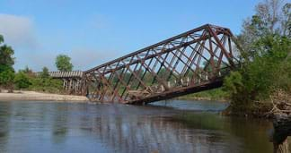 A photograph shows a collapsed steel truss bridge with one end sinking into the middle of a small river.
