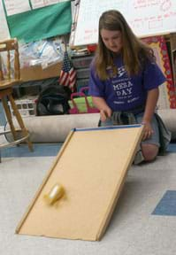 A young person kneels on the floor near a ramp made from a propped-up (angled) piece of wood. They have released a small wheeled vehicle from the top of the ramp, which rolls down the ramp towards the linoleum floor.