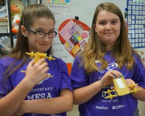 Two young people stand in a classroom, each smiling and holding in their hands four-wheeled vehicles made of dry pasta.