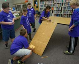 A photograph shows six youngsters in a classroom clustered around a board ramp from the table to the floor. One girl uses a wooden skewer to push a white Ping Pong ball down the ramp while a boy kneeling near the ramp bottom holds an envelope to catch the ball.