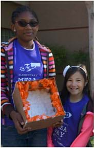 A photograph shows two girls wearing Elementary MESA Day shirts standing next to each other, looking at the camera. One holds her egg catcher made of cotton balls and crumpled tissue paper lining the inside of a cardboard box.