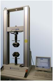 A photograph shows a desktop machine shaped like the frame of a tall open window with two sensors positioned from above and below that squeeze material placed between them. The force of the squeeze and the response of the material are recorded by a computer nearby.