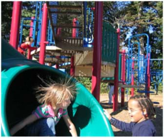 A photograph shows two young girls at a playground. One has just come down a plastic tube slide, and due to static electricity, her fine blond hair stands up in all directions around her head.