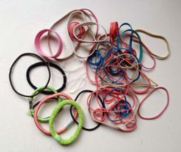 A photograph shows a pile of rubber bands of different colors, sizes, widths and materials, including elastic hair ties.
