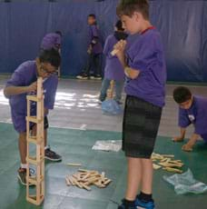 A photograph shows two boys using long, rectangular-shaped blocks as stacked columns and beams to make a tower on the floor. One boy is observing the other as he carefully places a block.