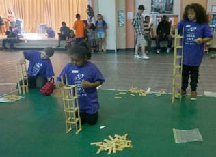 A photograph in a large room shows two girls and a boy individually stacking blocks on top of each other to make their own tall towers.