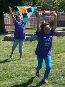 A photograph shows two young girls in a grassy playground attempting to launch a kite. One girl tosses a multi-celled tetrahedron kite high into the air as her partner runs ahead of her holding above her head a spool of string connected to the kite.