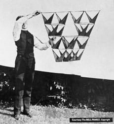 A black and white photograph shows a man using two hands to hold up and away from his body a 16-celled tetrahedron kite. The design includes opposing triangular vanes and was photographed outside against a white sheet.