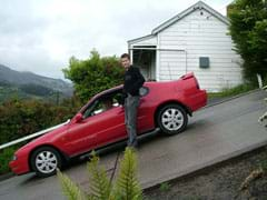 A photograph shows a man standing next to a sports car that is parked on a very steep hill.