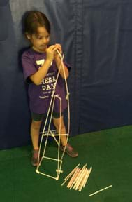 A photograph shows a young girl using plastic drinking straws and tape to build a tower structure that is almost as tall as she is.