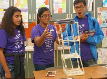 A photograph shows three students as they are adding magazines to the top of a 3-foot-tall straw tower on a desk to see how much weight it can hold.