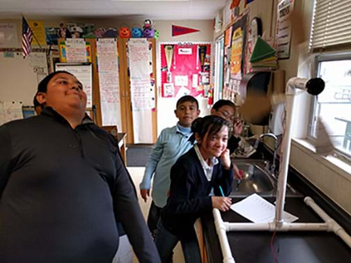 A photograph shows four smiling youngsters standing at the side of a counter in a classroom where a model wind turbine is set up and spinning, its blades a blur.