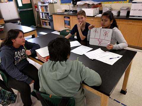 A photograph shows four youngsters sitting around a table. One girl holds a small whiteboard to show the other three kids three different wind turbine sketches.
