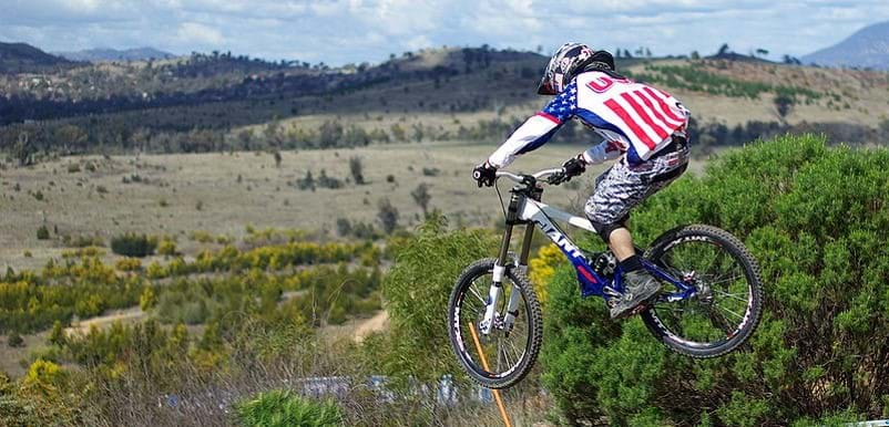 A picture of a person wearing a red, white, and blue shirt midair on a bike.