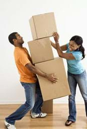 A photograph shows a man precariously carrying two large boxes while a woman places a third box on top of them.