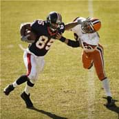 A photograph shows a football player with the ball giving a stiff-arm to another football player.