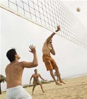 A photograph shows three boys in swimming trunks on a beach jumping and using their hands to redirect a volleyball over a net.